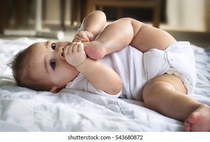 Baby lying down with foot in mouth
