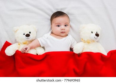 baby lying in his crib with his teddy bears aside