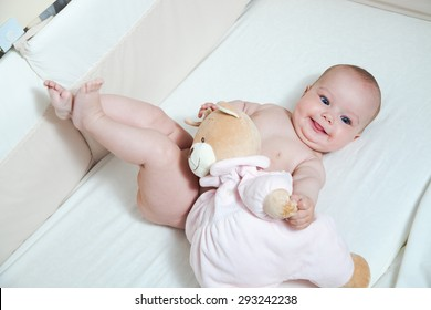 baby lying on the bed and playing with family