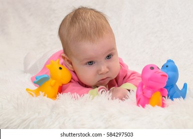 Baby lying on her belly on a white fur rug and playing with colored rubber toy dinosaurs