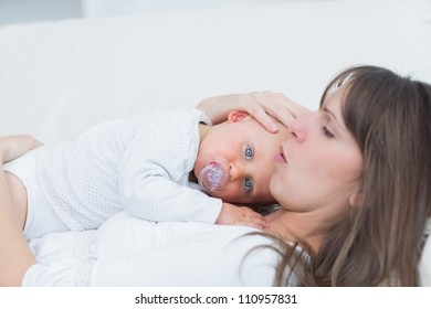 Baby lying on his mother in living room