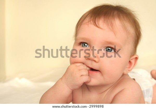 baby lying on tummy on white bed sheets chewing his/her fingers