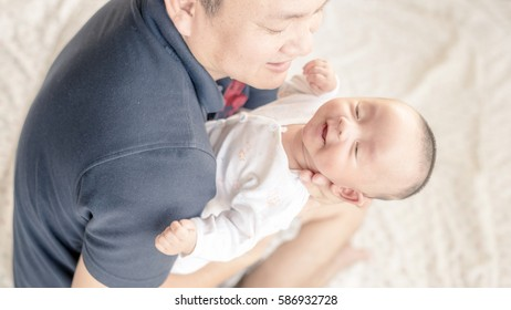The baby was lying on a white bed . That baby was teasing by his cute father and sister .This Image is showing very good relationships between family members.