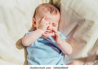Baby lying in the sun angry and crying calling his parents.