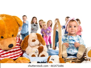 Baby with many teddies with many people behind
