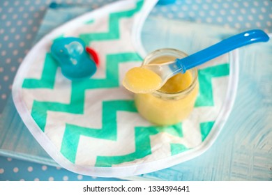baby mashed with spoon in glass jar