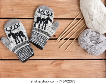 Baby mittens knitted in white/ gray/ black yarn with yarn for knitting and knitting needles on a wooden background. Figure with a deer. Top view. Flat lay. Handmade for winter woolen cloth.
