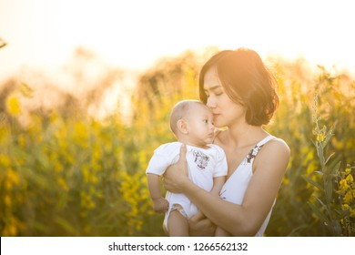 Baby and Mom having fun in yellow flowers field with golden light.