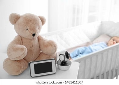 Baby monitor, camera and toy on table near crib with child in room. Video nanny