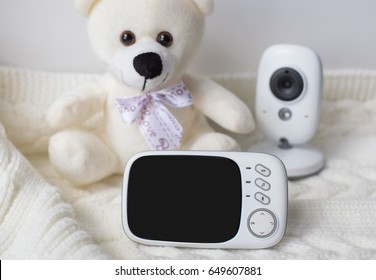 baby monitor for security of the baby surrounded by a teddy bear on a light background. close-up