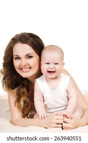 Baby and mother, childhood, motherhood, happy family. Young mother with baby boy. Sitting on white cloth and having fun