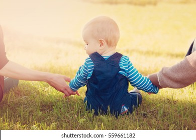Baby with mother and father holding hands on the nature