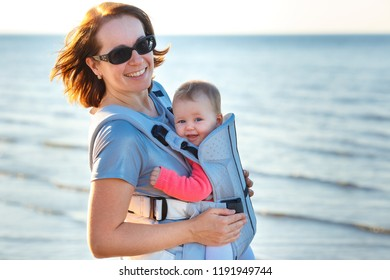 Baby and mother on sea at summer day. Happy family walking on nature outdoors. Child in a carrier backpack
