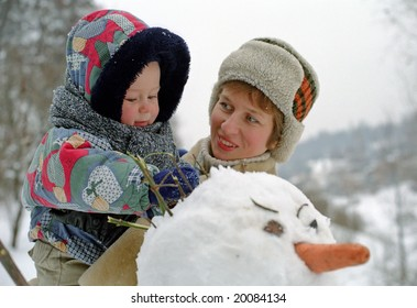 baby and mother play with snowman