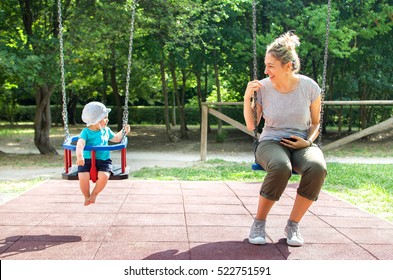 baby mother swing playground looking each other family happy moments