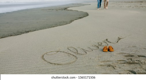 Baby name Oliver written in the sand next to his shoes while the parents take a walk