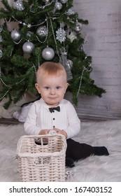 Baby near christmas tree on fur carpet