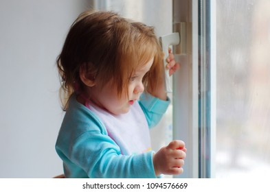 baby near the window. toddler holds the handle and looking out the window