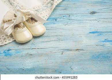 Baby newborn background,  vintage newborn clothes and shoes for baptism on wooden background , blank space for message