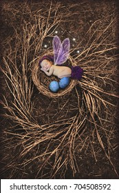 Baby newborn Fairy with stocking cap and purple wings sleeping in bird nest with blue eggs/Newborn Baby Fairy with purple wings sleeping in bird nest