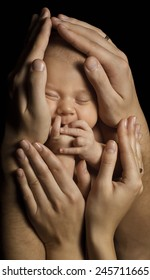 Baby Newborn in Parents Hands Sleeping. Family Concept. Child Birth. Black Background.