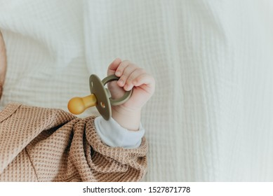 Baby with a nipple. Close up of baby hands with pacifier. Focus is on hands. Newborn sleeping on a blanket holding a pacifier in his hand.