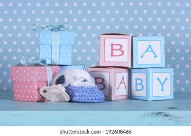 Baby nursery bootie, dummy pacifier and baby letters pink and blue gift boxes against a vintage aqua blue table and polka dot background for baby shower or newborn girl greeting card.