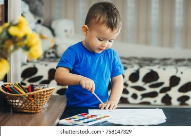 the baby in the nursery, on the black table in the blue shirt, with enthusiasm draws paints
