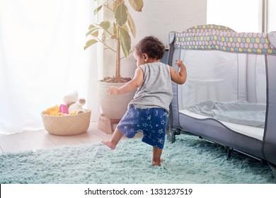 Baby in nursery walking with unstable steps, learning childhood development milestone