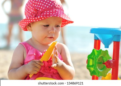 baby on the beach playing with toys