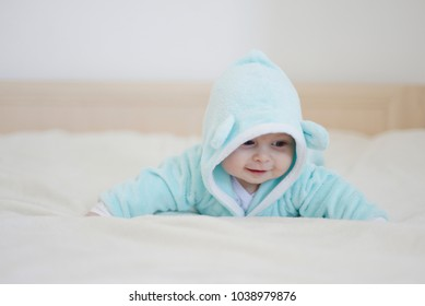 baby on the bed in a bear suit