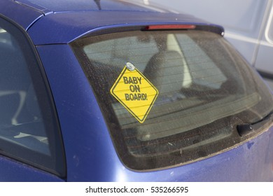 baby on board on the back car glass yellow