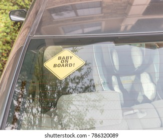 Baby On Board sticker on the car back windows. A blurred image of car seat is available in background.