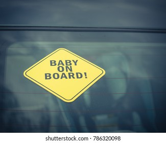 Baby On Board sticker on the car back windows. A blurred image of car seat is available in background. Vintage tone.