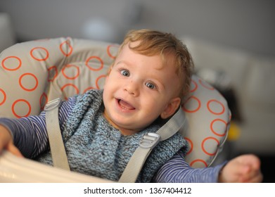 Baby on a feeding chair laughing
