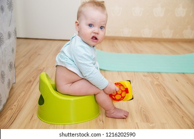 Baby on the potty. The child of the first year of life sitting on a potty in the room. - Shutterstock ID 1216202590
