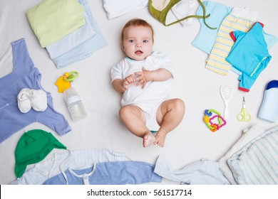 Baby on white background with clothing, toiletries, toys and health care accessories. Wish list or shopping overview for pregnancy and baby shower.
