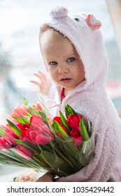 baby on the window with flowers