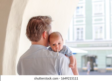 Baby over feeding. Newborn boy vomiting while his dad carrying him on outdoor background. Mixed race infant Asian-German.