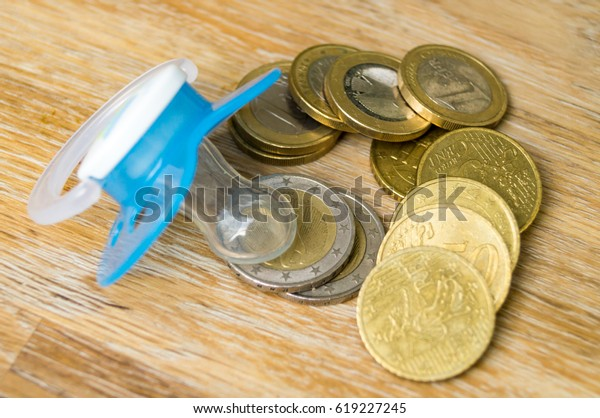 Baby pacifier with euro coins on wooden background