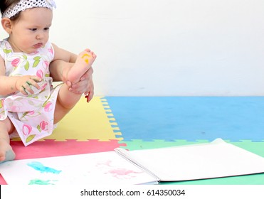 Baby painting her  foot print in a notebook