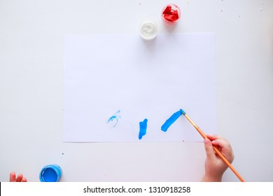 Baby painting picture for mother. Mother's day picture. Baby hands. Baby fingers in paint. Baby holds the brush. White paper.