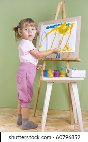 Baby paints at the easel painting