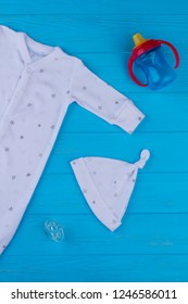 Baby pajama sleepwear and knot hat. Bottle, pacifier on blue wood.