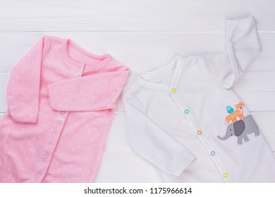 Baby pajamas outfit. White wood background.