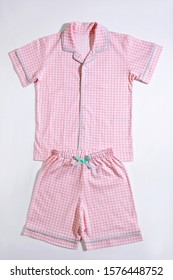 Baby pajamas. Sleeping outfit for baby girl. Pajamas in pink and white colors, square pattern. On white background