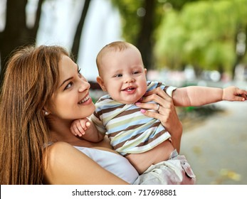 Baby in park outdoor. Kid on mom's hands. Happy beautiful mom and child summer sunrise or sunset on city outside. Portrait of happy loving mother and her son spring outdoors. Adoption of the child.