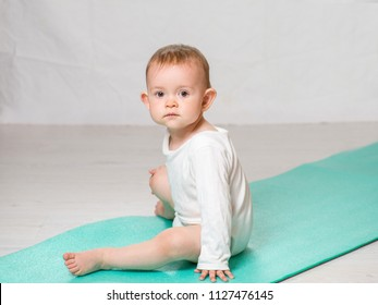 the baby is performing physical exercises on the yoga mat. Baby Yoga