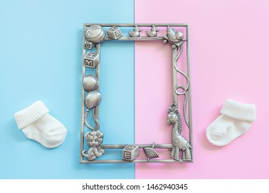 Baby photo frame and  baby socks on blue and pink background. Motherhood concept. Guessing unborn baby gender Girl or boy. Top view, layout, flat lay composition. Copy space for text.