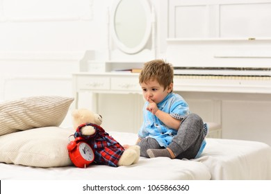Baby playing bear playing on white bed. Kid put toy in bed for sleep, shows gesture to be silent. Teddy bear sleeps near alarm clock.